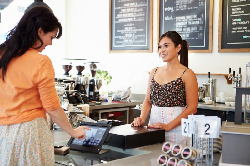 Female Owner Of Coffee Shop Serving Customer