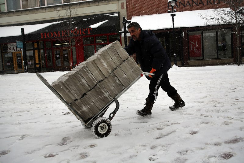 A newspaper deliverer wheels a trolley of newspapers through the snow