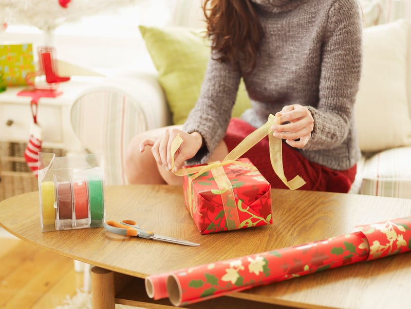 A woman ties a bow on a wrapped present with tape, scissors and a roll of wrapping paper lying on the table nearby