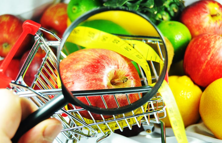 inspecting fruit with magnifying glass at grocery store