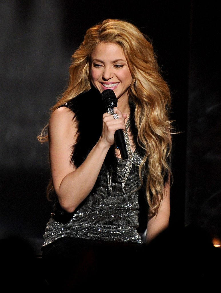 Shakira speaking into a microphone