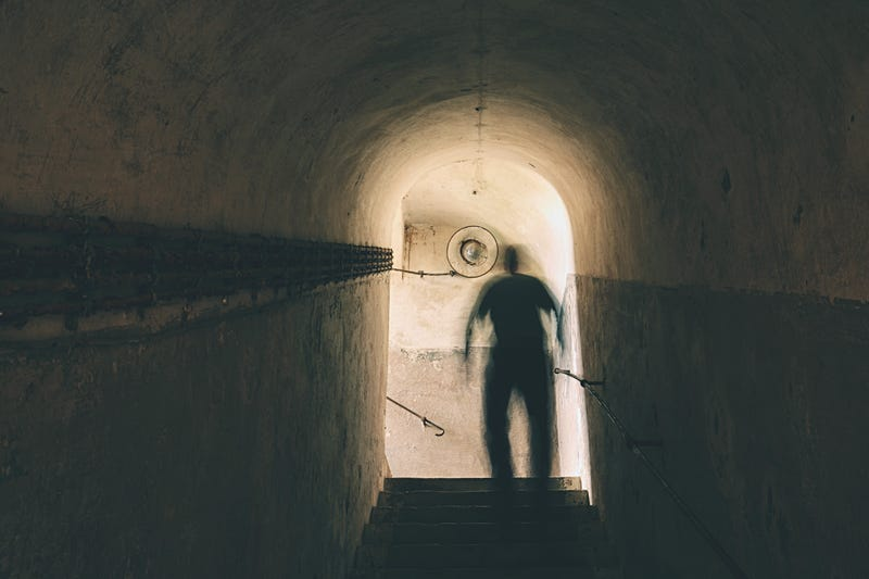 Man is walking through dark underground.
