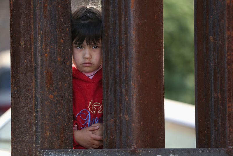 A child on the Mexican side of the U.S.-Mexico border fence looks into Arizona