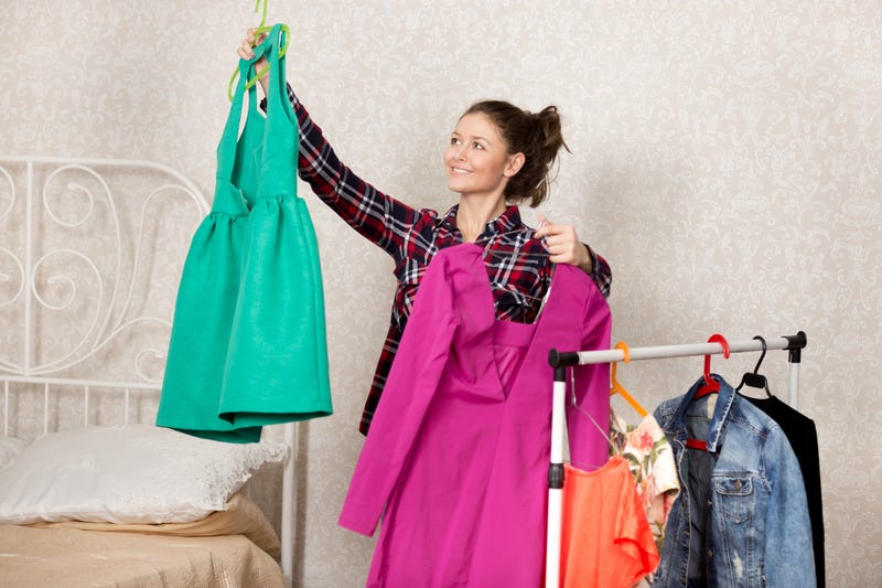 woman holds up dress in bedroom