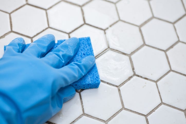 gloved hand cleaning grout with a sponge