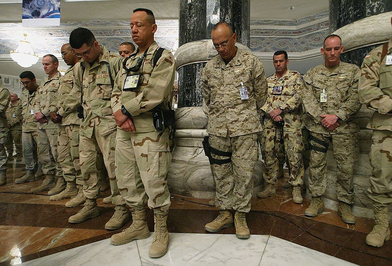 Soldiers pause for a moment of silence during a Memorial Day ceremony in Iraq in 2004