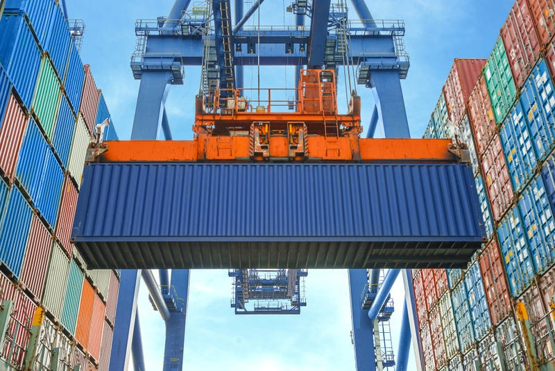 A shipping container lifted by a crane at a port