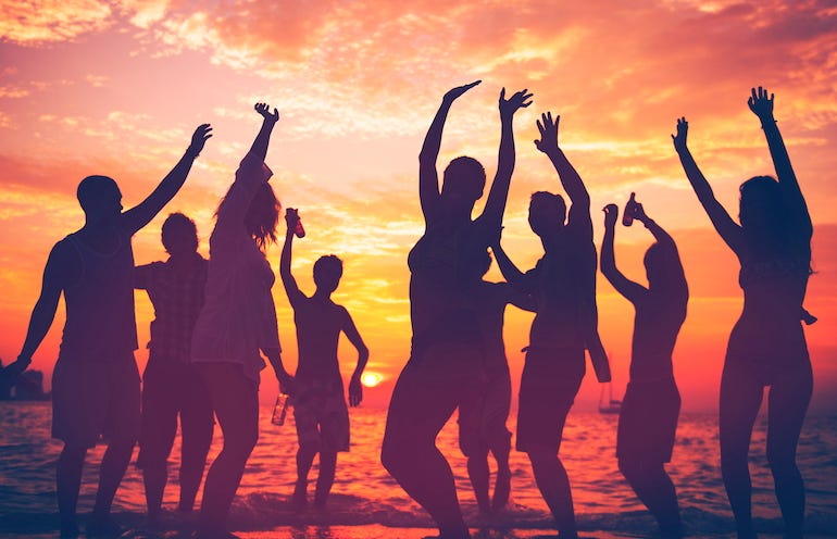 People partying on beach during sunset