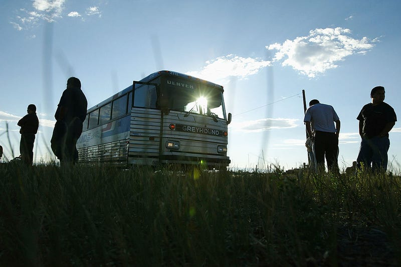 Passengers stand on the roadside during a short Greyhound bus layover in Wyoming