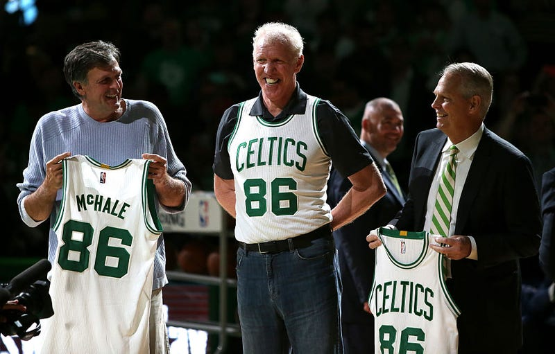 Kevin McHale (left) holds up an honorary jersey with former teammates.