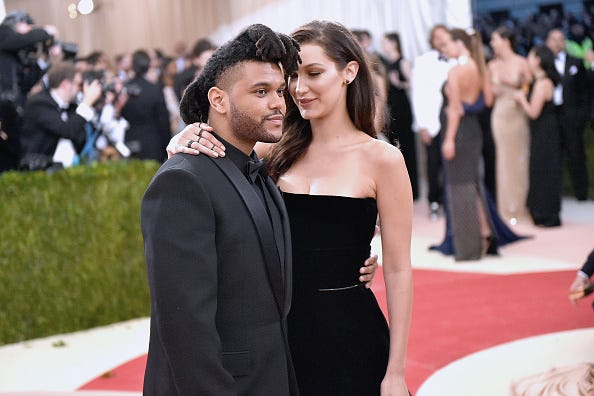 The Weeknd and Bella Hadid attend a red carpet event.