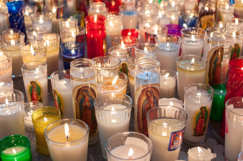 Hundreds of glass vase religious candles featuring the Virgin Mary as Our Lady of Guadalupe lit on church floor in Mexico