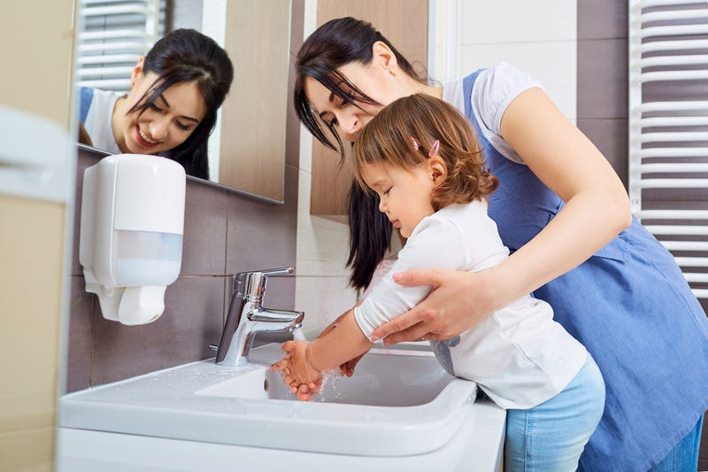 A mom helps her daughter wash her hands