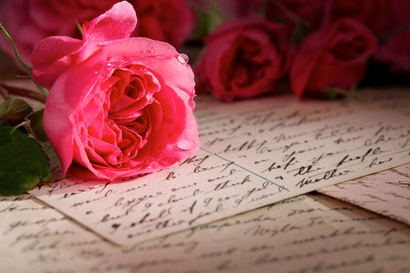 A bunch of roses lies on top of hand written notes