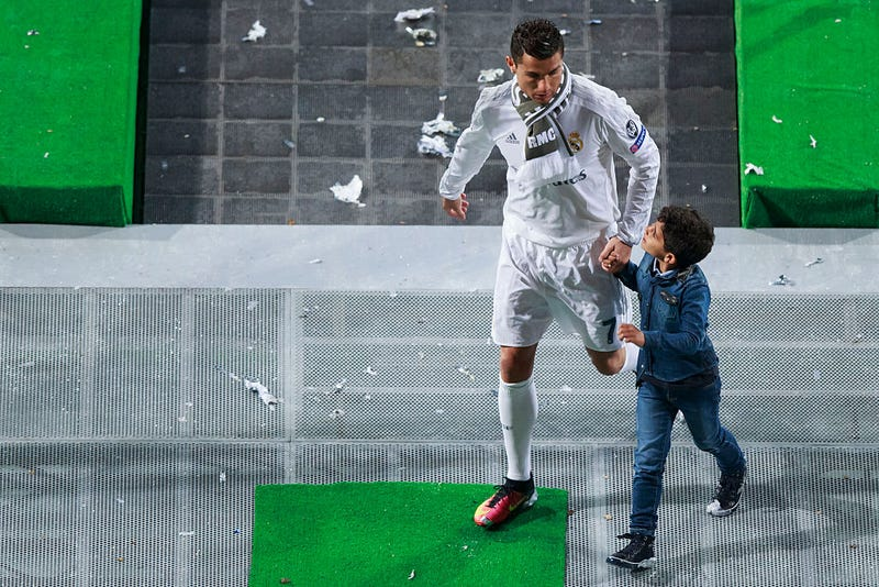 Cristiano Ronaldo (L) of Real Madrid CF leaves the pitch with his son Cristiano Ronaldo Jr. (R) after the celebration with their fans at Santiago Bernabeu Stadium the day after winning the UEFA Champions League Final match against Club Atletico de Madrid on May 29, 2016 in Madrid, Spain.