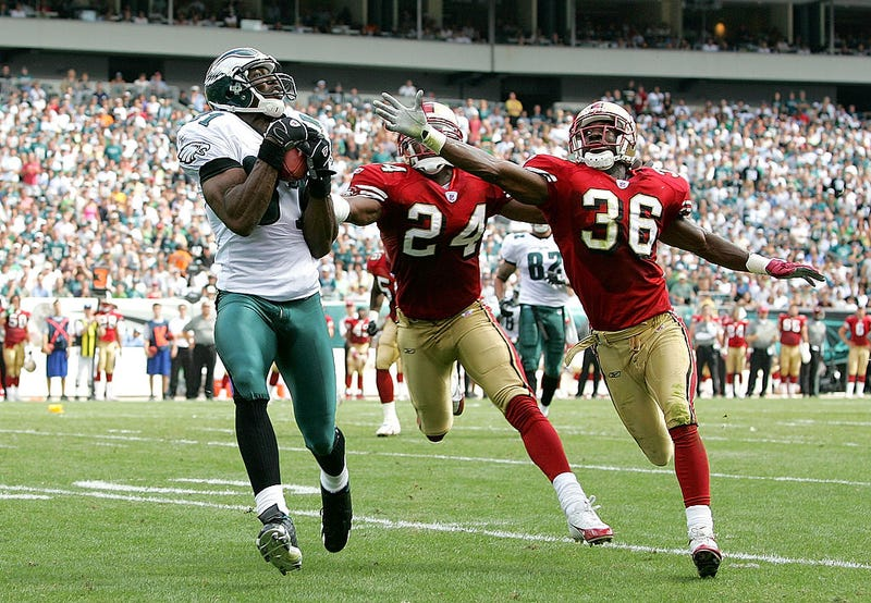 Terrell Owens catches a pass over a duo of 49ers defensive backs.