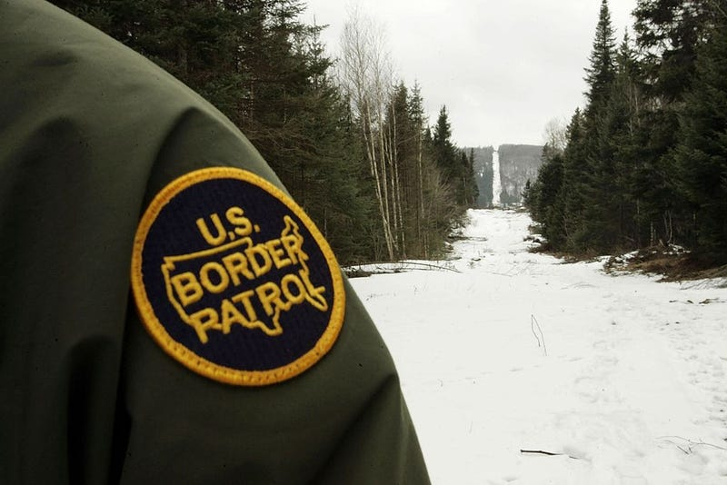A U.S. Border Patrol agent stands along the boundary marker cut into the forest marking the line between Canadian territory on the right and the United States March 23, 2006 near Beecher Falls, Vermont. As American politicians continue to debate immigration reform, Border Patrol agents work the northern border to prevent illegal entry.