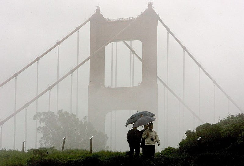 A group of men walk through the rain near the north tower of the Golden Gate Bridge April 12, 2006 in Sausalito, California.
