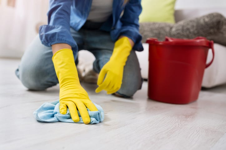 A woman cleans a floor with a water bucket and a rag