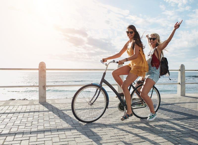 girl friends riding bike having a blast at the beach