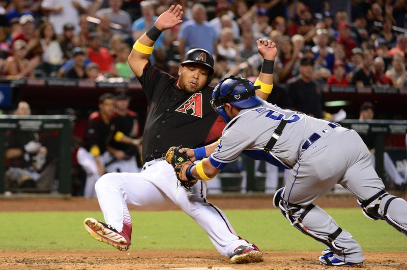 Yasmany Tomas tries to avoid a tag at home plate
