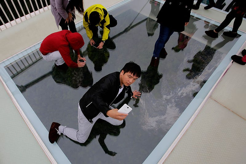 Tourists take pictures with their iphone on the glass-floor suspension bridge