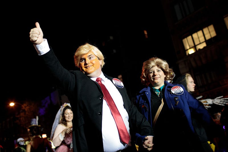 A pair dressed as Donald Trump and Hillary Clinton walk with revelers along Sixth Avenue during the 43rd annual Village Halloween Parade, October 31, 2016 in New York City.