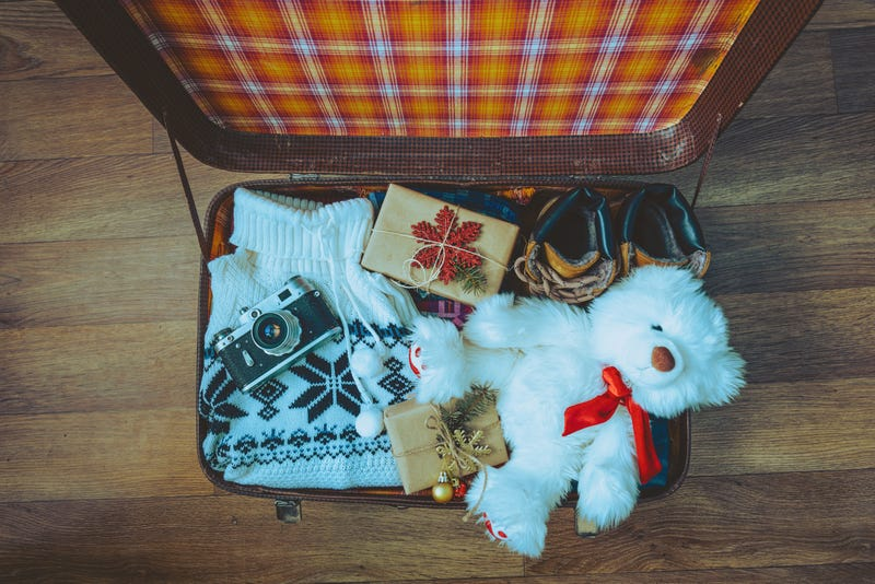 From above, an open suitcase loaded with a sweater, a stuffed bear, a camera, and wrapped gifts