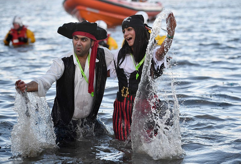 A couple dressed as pirates splash around in the water as they join around 1,000 New Year swimmers, many in costume, in front of the Forth Rail Bridge during the annual Loony Dook Swim in the River Forth on January 1, 2017 in South Queensferry, Scotland.