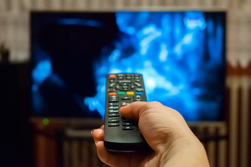 hand holding remote control pointed at television