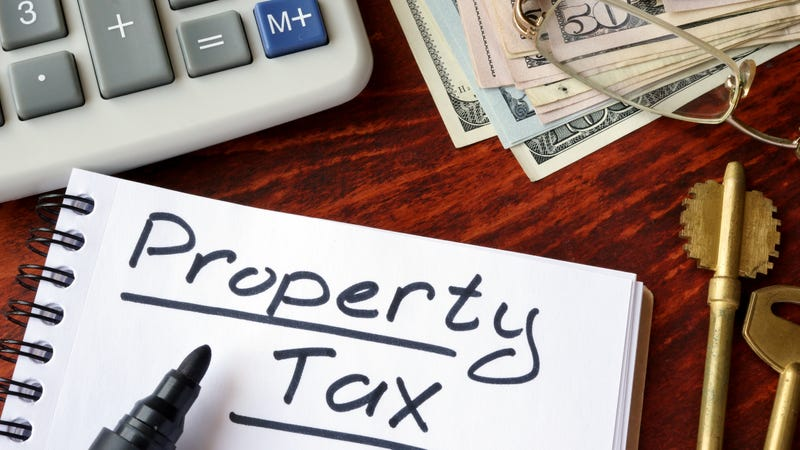 Property tax written in a notebook and calculator