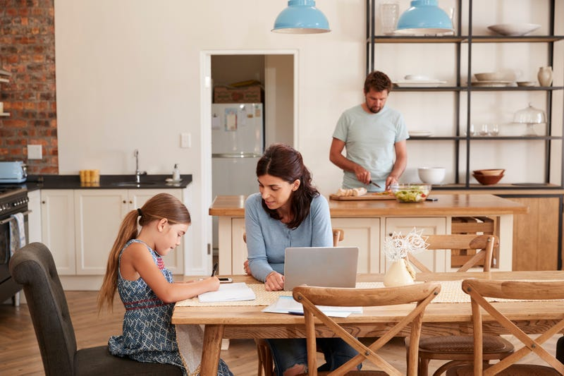 A mother helps her daughter with homework while a father works in the kitchen in the background