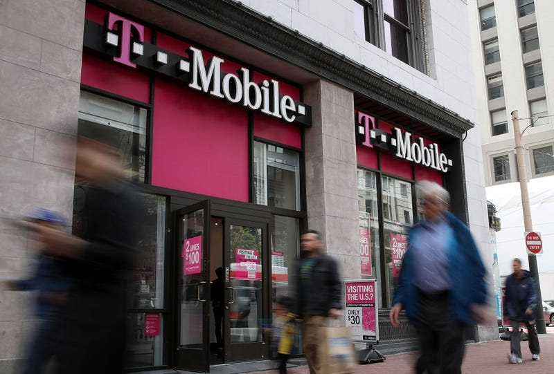 Pedestrians walk by a T-Mobile store