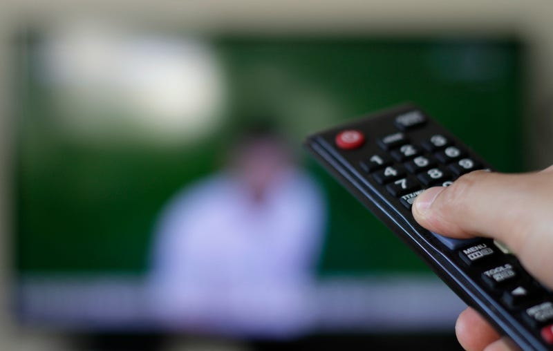 Remote control with TV set in the background
