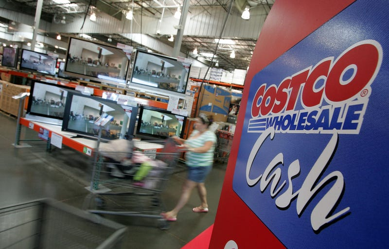 woman shopping for tvs using costco cash
