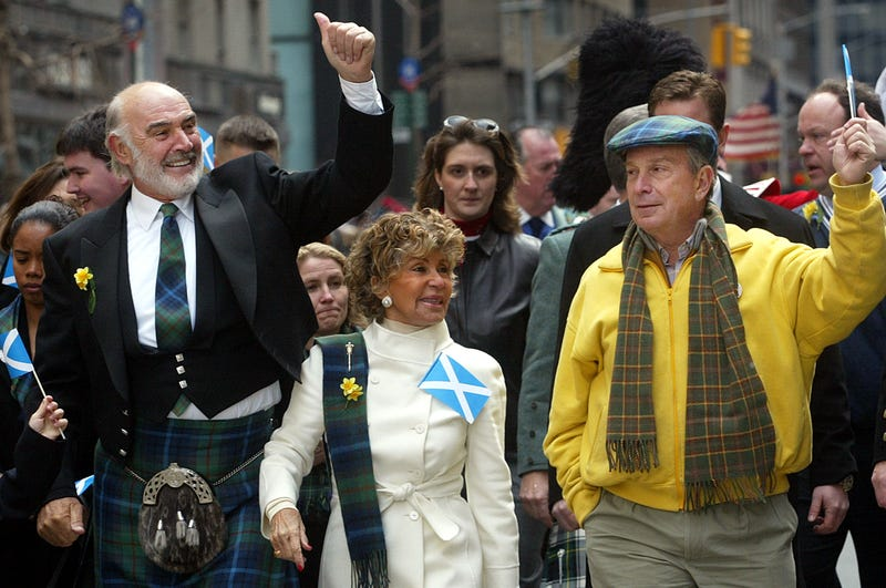Sean Connery (L), his wife Micheline Roquebrune and New York City Mayor Michael Bloomberg wave to the crowd as they march up Sixth Avenue during the world's largest pipe and drum parade to celebrate Scottish Tartan Day April 6, 2002 in New York City. Approximately 10,000 participants marched in the parade which was led by Connery.