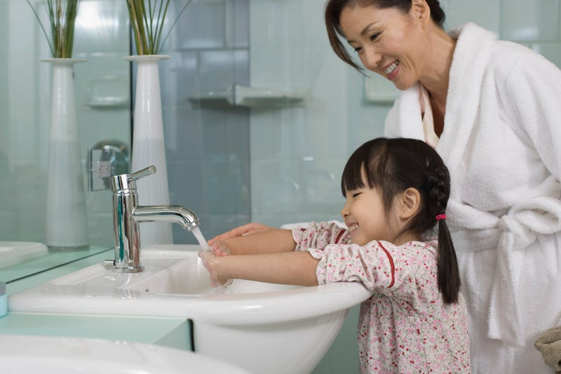 A mother stands over her daughter as she washes her hands in a sink