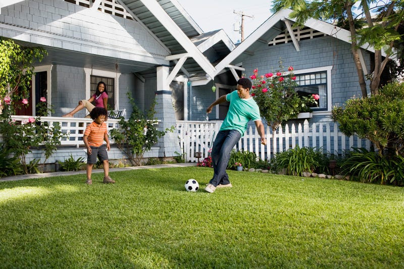 A father and son kick a soccer ball in a yard while a mother looks on