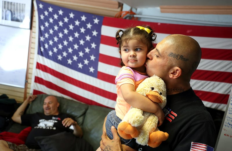 """Deported U.S. Marine Corp veteran Mauricio Hernandez, who served in Afghanistan, kisses his daughter Emily Hernandez as he visits the Deported Veterans Support House on July 4, 2017 in Tijuana, Mexico. The Deported Veterans Support House, also known as """"The Bunker"""" was founded by deported U.S. Army veteran Hector Barajas to support deported veterans by offering food, shelter, clothing as well as advocating for political legislation that would prohibit future deportations of veterans. There are an estimated 11,000 non-citizens serving in the U.S. military and most will be naturalized during or following their service. Those who leave the military early or who are convicted of a crime after serving can be deported. (Photo by Justin Sullivan/Getty Images)"""