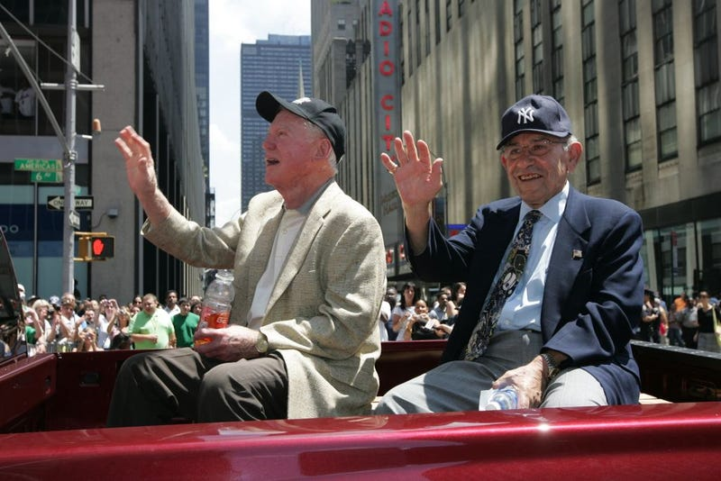 Whitey Ford and Yogi Berra sit in the back of a car during a parade