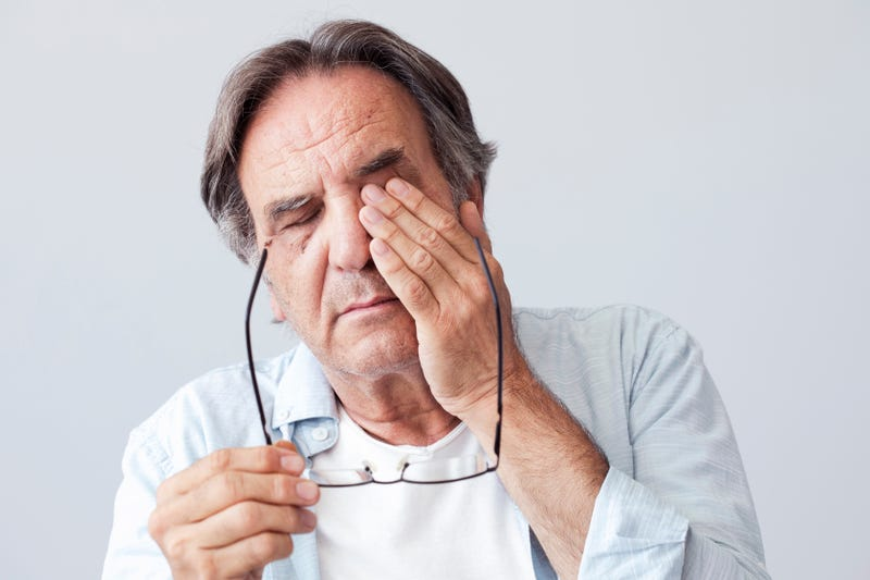 An old man rubs his eyes