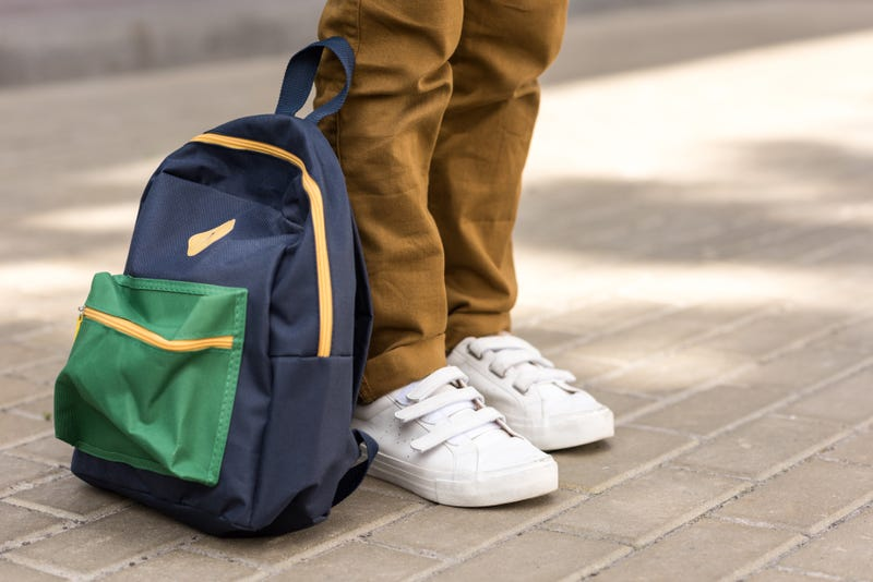 student stands with backpack at his feet