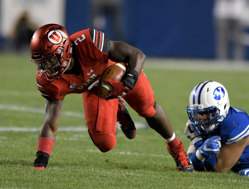 Utah's Zack Moss tries to stay on his feet