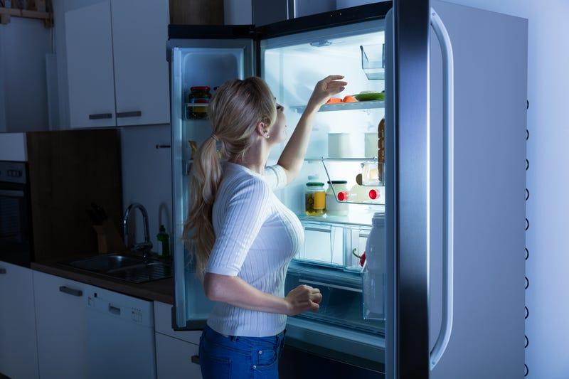 woman looking for food in fridge