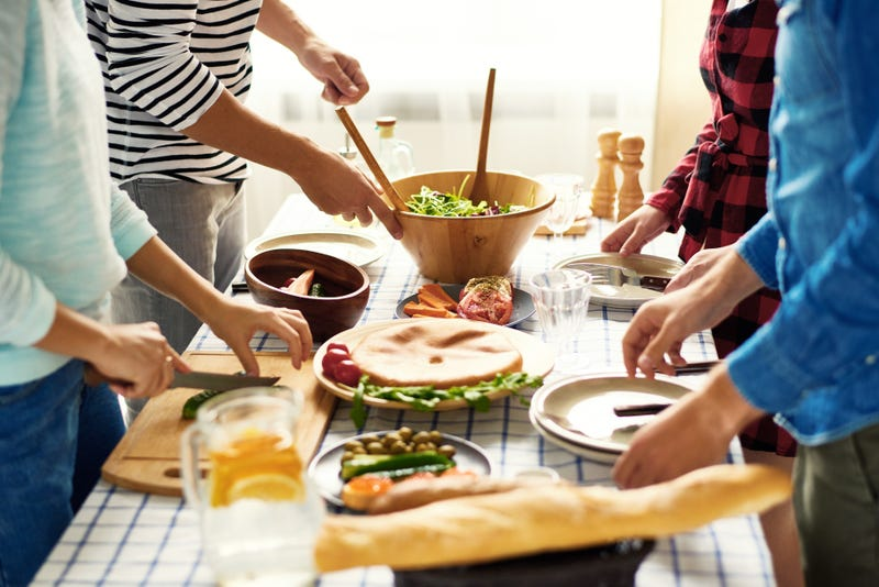 Four friends prepare various ingredients on a table
