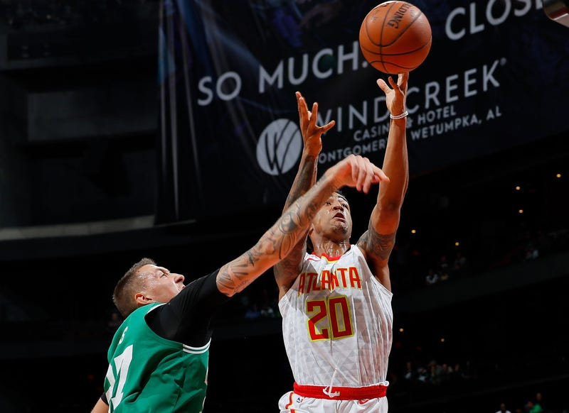 John Collins shoots over Daniel Theis' outstretched arm.
