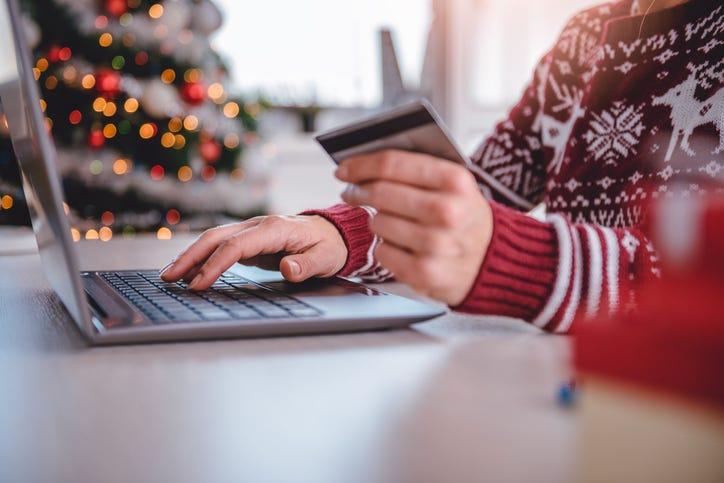 Persona hace compras en una computadora en frente de un arbol de navidad.