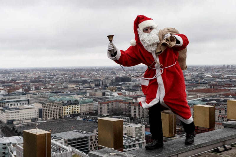 santa jingling bell with bag of gifts on rooftop
