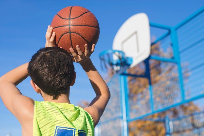 boy practices basketball