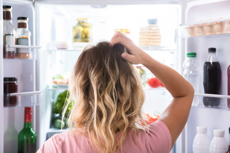 A confused woman stands in front of an open refrigerator